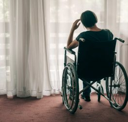 woman in wheelchair looking out the window and thinking