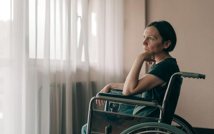 woman in worn wheelchair looking out the window and thinking