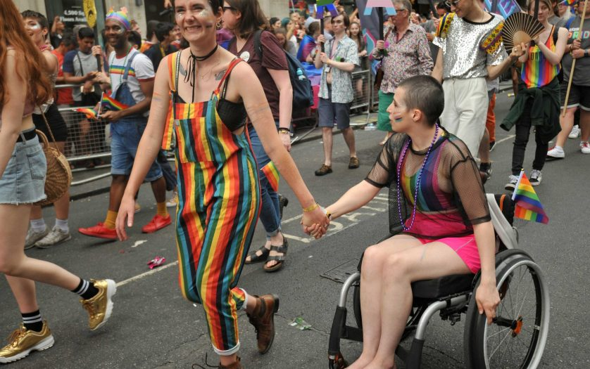 A woman walking together with her partner in wheelchair at the Pride parade