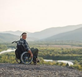 young man in a wheelchair enjoying fresh air in sunny day on the mountain