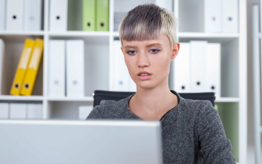 Girl with short blond hair is sitting at her workplace and looking at laptop screen.