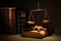 Legislation concept. Old brass weight scale and ancient books under beam of light on dark background