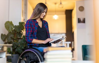 Young woman in wheelchair reading a book