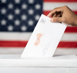 Concept of Mail in vote at US election - hands dropping mail inside the ballot box with us flag as background