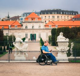 man tourist in wheelchair traveling in Europe. Lower Belvedere at background, Vienna, Austria