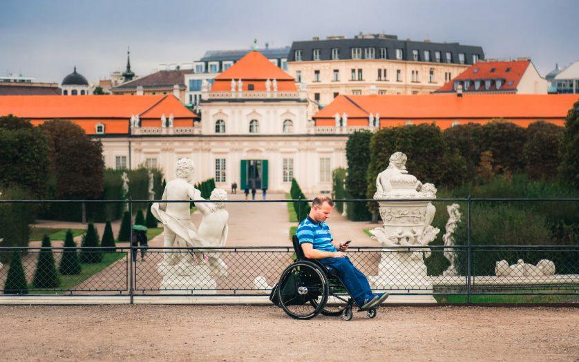 man tourist in wheelchair traveling in Europe. Lower Belvedere at background, Vienna, Austria