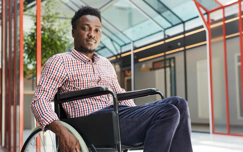 Portrait of African young disabled man sitting in wheelchair at office building