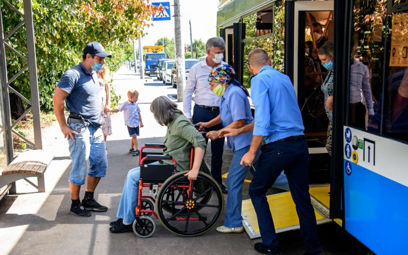 A passenger with disabilities gets off the bus