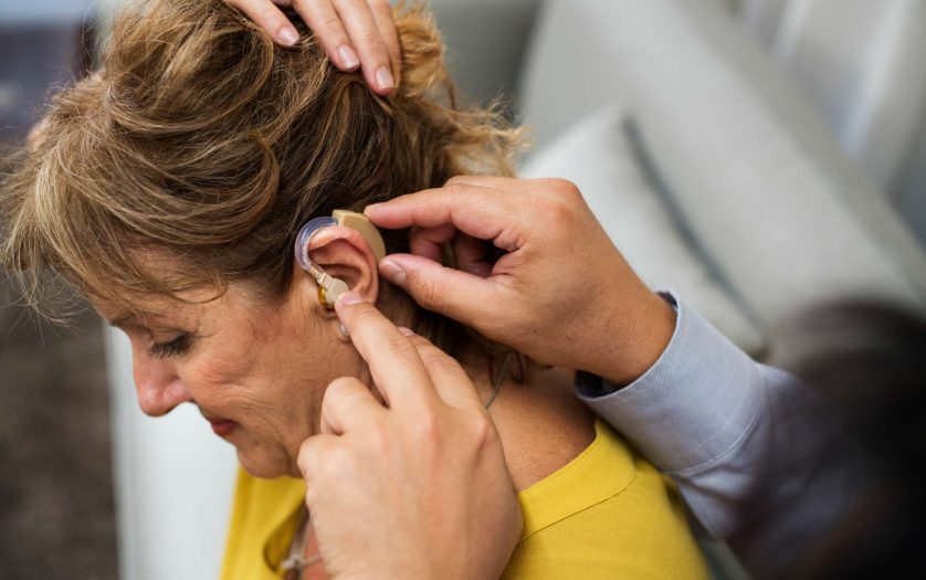 A doctor inserting hearing aid to a patient's ear