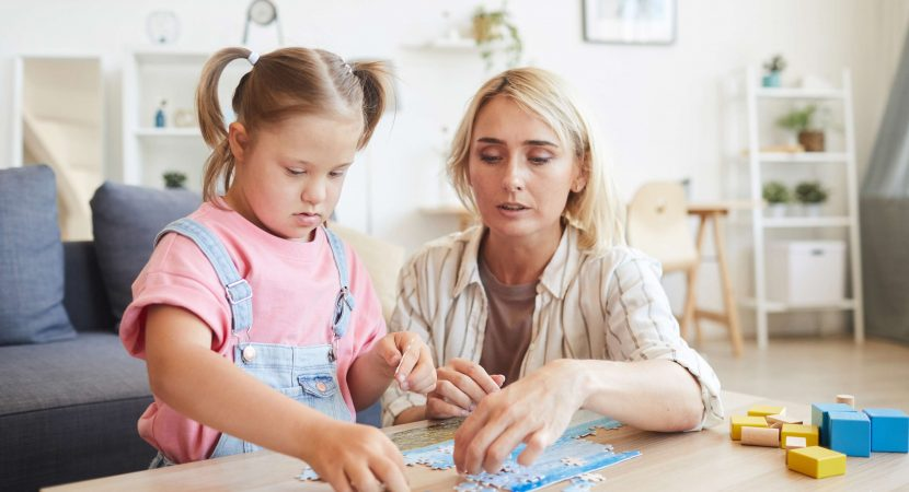 Young mother helping to her daughter with down syndrome collecting puzzles at the table in the room