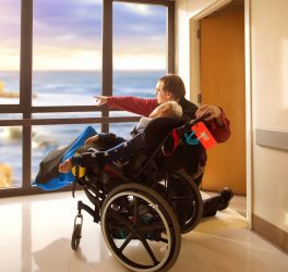 Father kneeling next to disabled son in wheelchair looking out hospital window at ocean and cliffs outdoors.