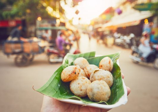 Hand of man holding bowl with sweet coconut food. Busy street full of restaurants, bars and shops - Siem Reap, Cambodia