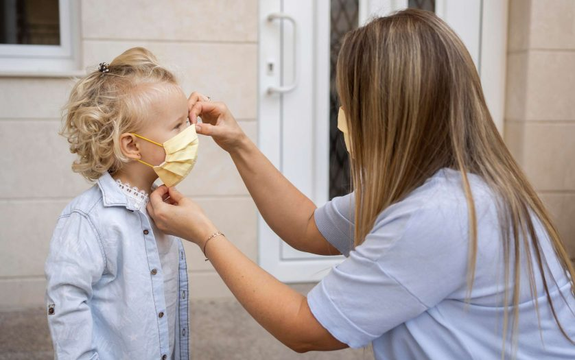 Side view of mom putting medical mask on child