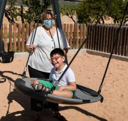 Child with disability in swing with mother pushing, wears blue mask of pandemic coronavirus protection.