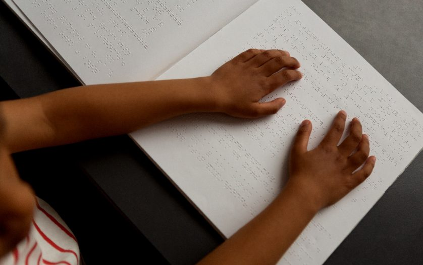 schoolboy hands reading a braille book in classroom