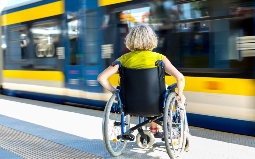 Woman sitting on wheelchair on a train platform ready to get in to the train