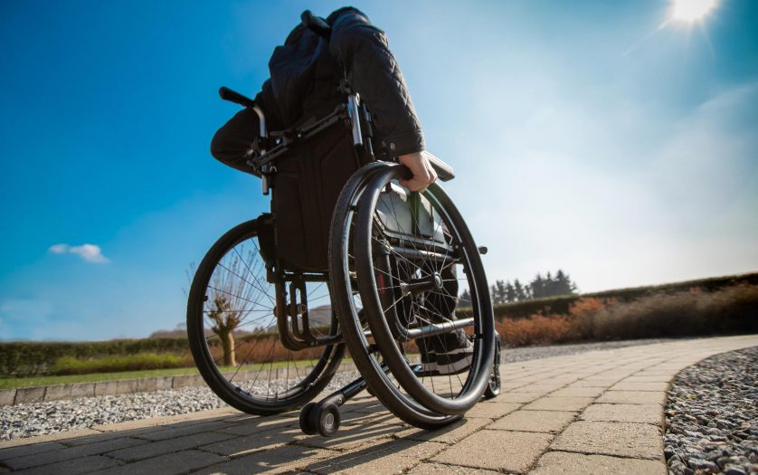 Disabled man in wheelchair outdoor in the sun