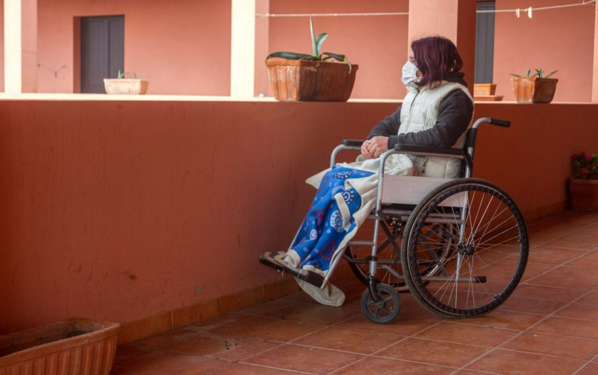 Disabled woman alone in a wheelchair with a protective mask looking out from the balcony of the house staying home for the quarantine
