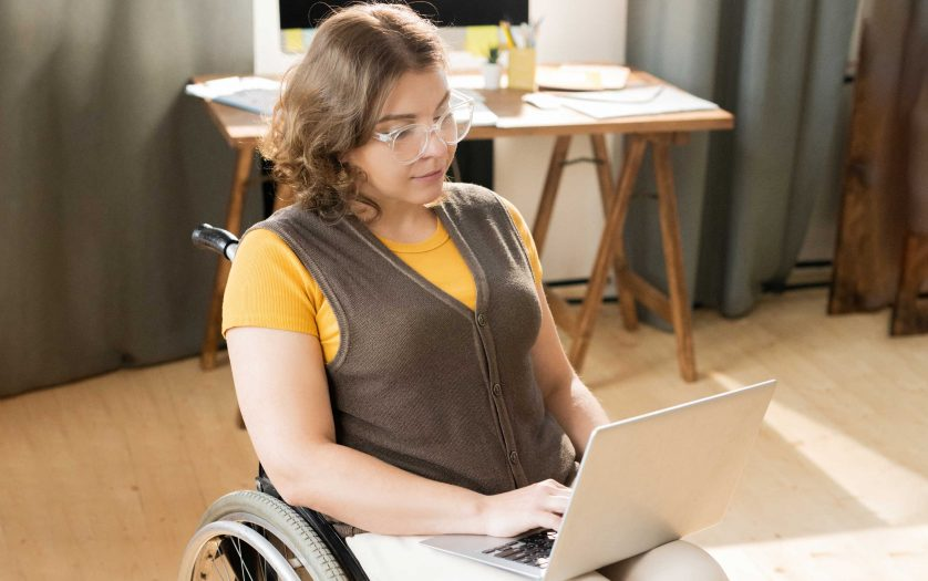 Young woman in wheelchair using computer at home