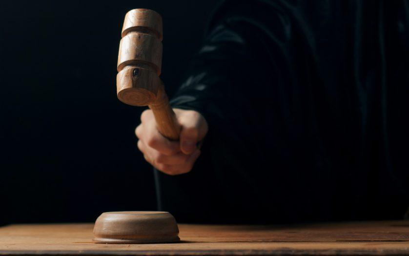 Hand banging gavel on dark background, the judge makes a verdict