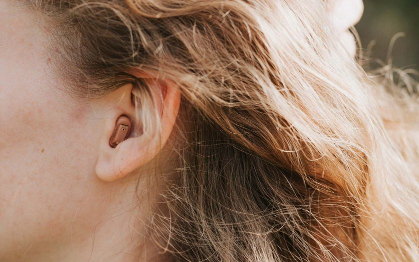 small intra channel hearing aid in the ear of a woman