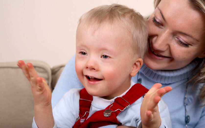 A closeup portrait of a mother holding her smiling and happy young son with Down Syndrome.