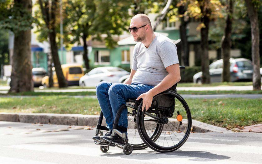 man in wheelchair crossing street road.