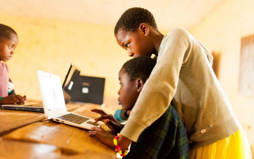Close up portrait of young african boy using computer