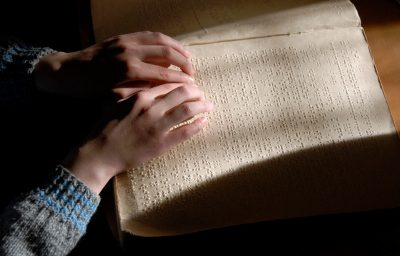 Blind person reading text in braille