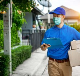delivery man in blue t-shirt carrying parcel box and document to sign in front of customer home.