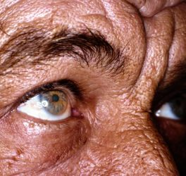 Close up of old man eyes, sun burned and wrinkled skin