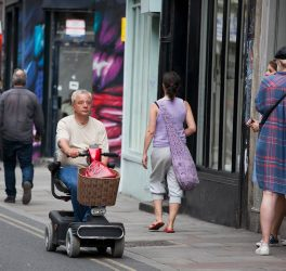 A man rides on a scooter for the elderly in Bricklane shopping, London, UK