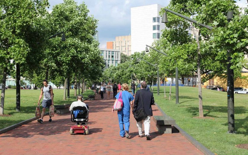Wheelchair user and people walk in campus of Pennsylvania State University in Philadelphia.
