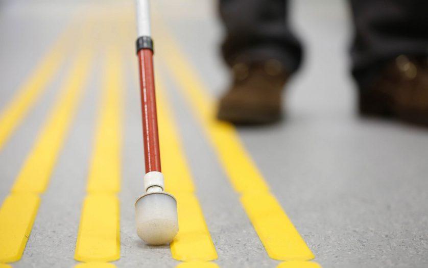 Blind pedestrian walking on tactile paving
