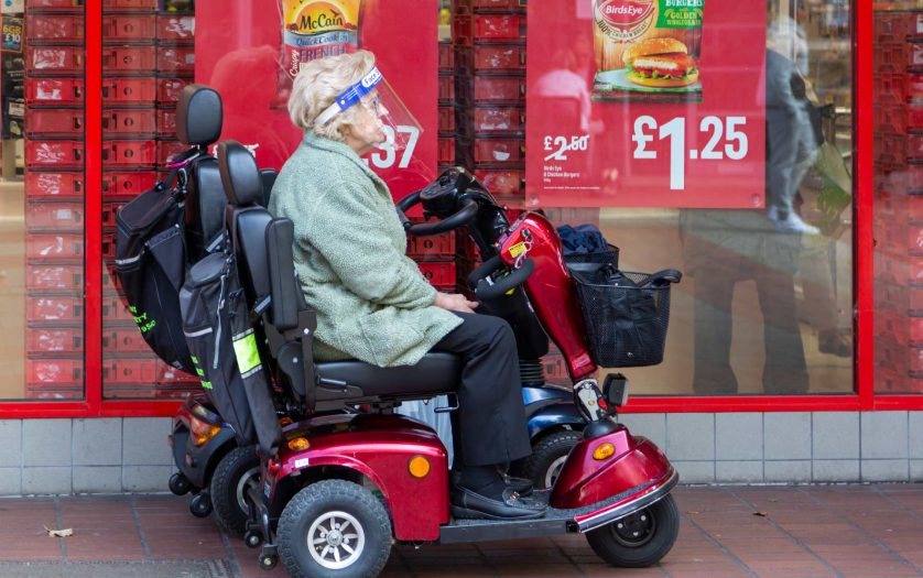 An elderly lady wearing a face shield sitting on a mobility scooter outside a supermarket during the coronavirus pandemic, Portsmouth, Hampshire, UK