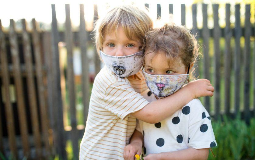 children with animal face masks playing outdoors