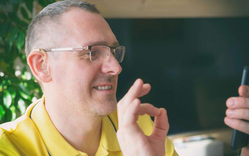 Deaf man talking using sign language on the smart phone