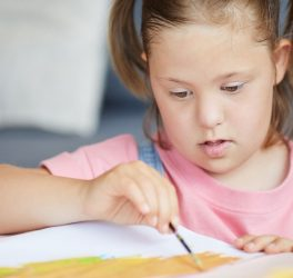 Child with down syndrome painting with paintbrush at the table at home