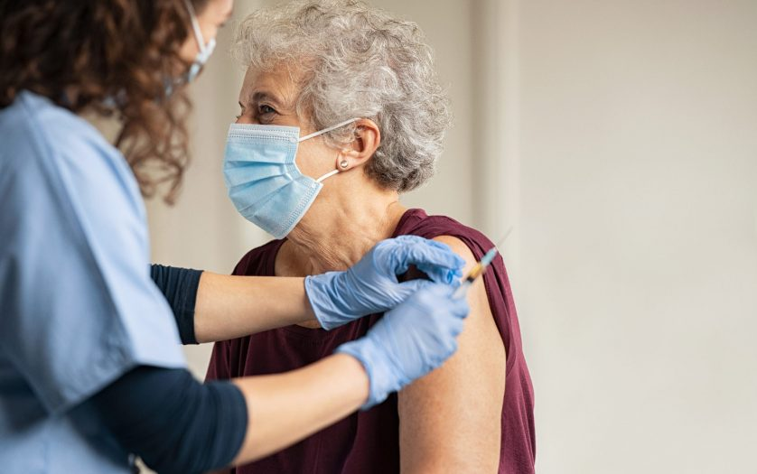 Doctor giving Covid vaccine to senior woman