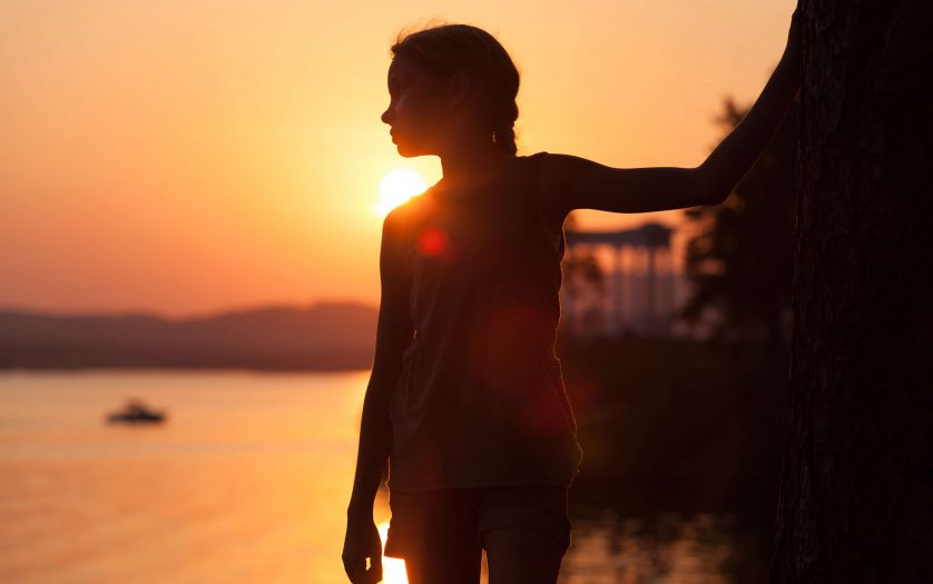 little girl standing on the beach at sunset time.
