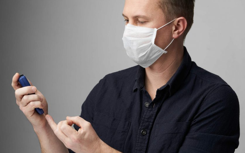 Young man with medical face mask measuring blood sugar level.