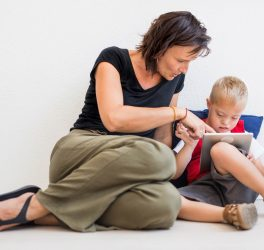 down-syndrome school boy sitting on the floor with mother, using tablet.