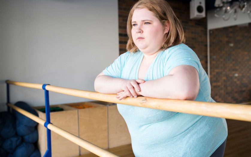 obese young woman standing at bar looking pensively at window