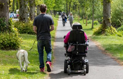 a carer and a support dog walking alongside a woman in an electric wheelchair