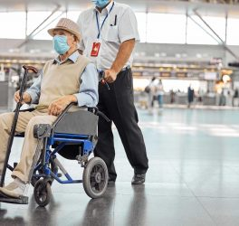 Airport worker rolling a old man in wheelchair