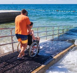 a person pushing a Man in wheelchair on accessible beach with ramp.