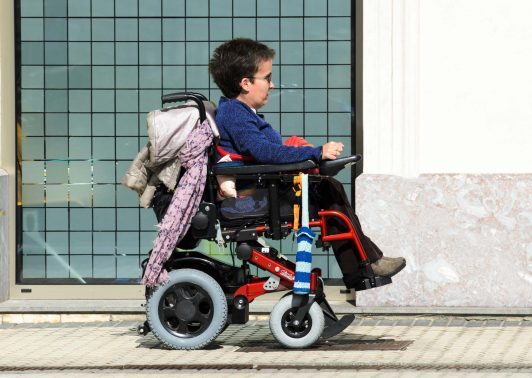 A young woman in a wheelchair, walking along a sidewalk in the city of San Sebastian, in the Basque Country (Spain)