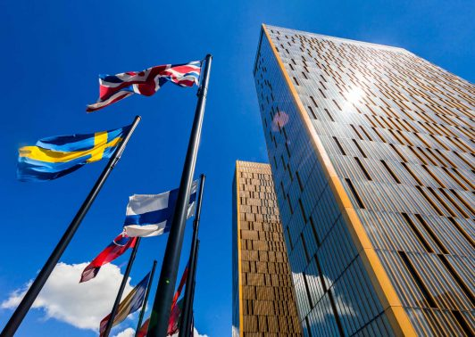 The two towers of the European Court of Justice and flag poles in Luxembourg against blue sky