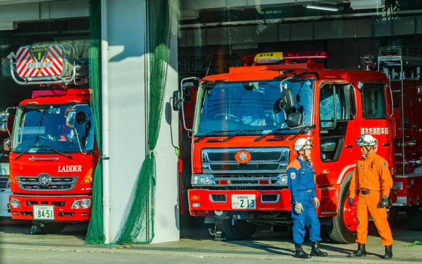 Two men talking at fire station in kanagawa prefecture, japan