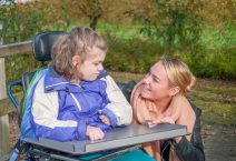 girl in a wheelchair being cared for by a care worker